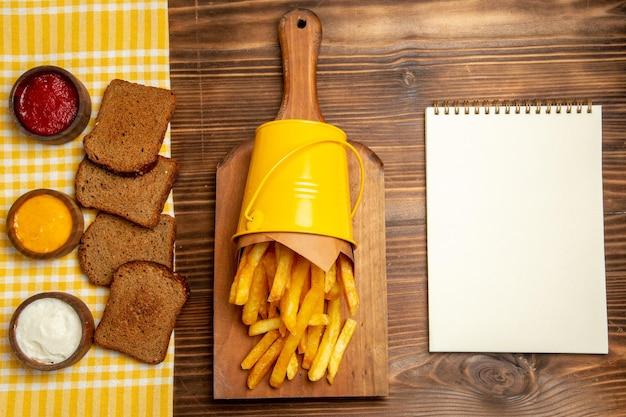 Draufsicht auf pommes frites mit brot und gewürzen auf braunem tisch