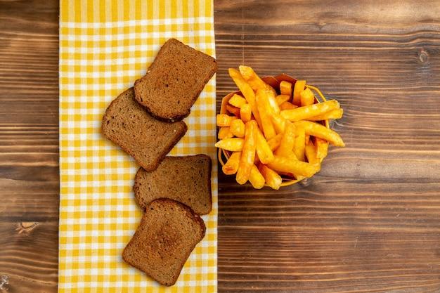 Draufsicht auf pommes frites mit dunklen brotlaiben auf braunem tischkartoffelbrot mahlzeit burger essen