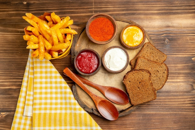 Draufsicht auf pommes frites mit gewürzen und dunklen brotlaiben auf braunem tischkartoffelbrot-mahlzeit-burger-essen