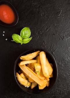 Draufsicht auf pommes frites mit ketchup-sauce und salz