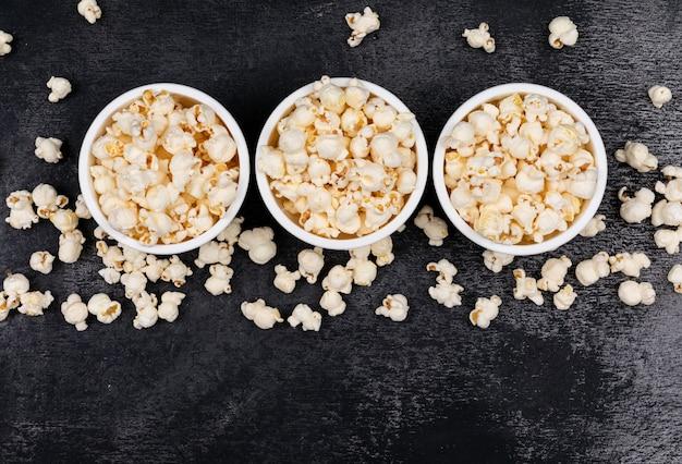 Draufsicht auf popcorn in schalen mit kopienraum auf schwarzer horizontaler