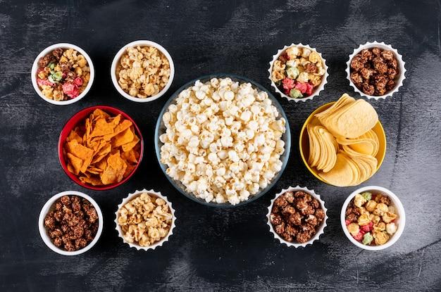 Draufsicht auf popcorn und chips in schalen auf schwarzer horizontaler