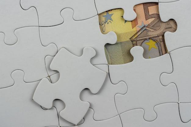 Draufsicht auf puzzleteile mit geld darunter - geschäftskonzept