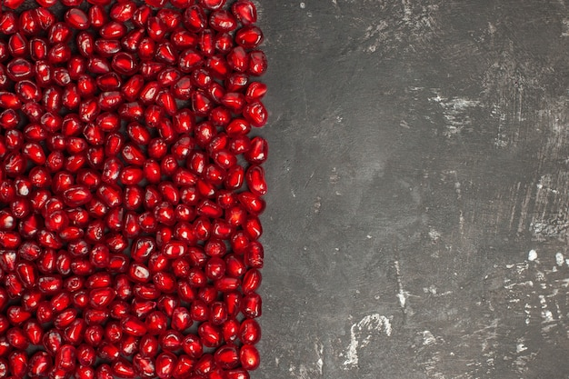 Draufsicht auf rechteckige granatapfelkerne auf dunkler oberfläche Kostenlose Fotos