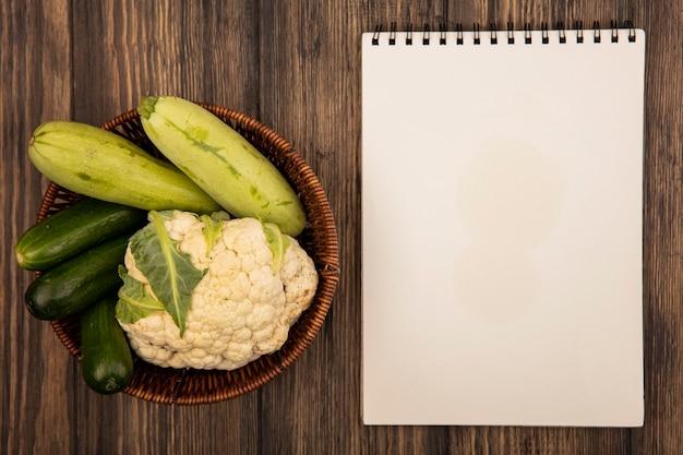 Draufsicht auf reich an vitamiins-gemüse wie zucchini-gurken-blumenkohl auf einem eimer auf einer holzwand mit kopierraum