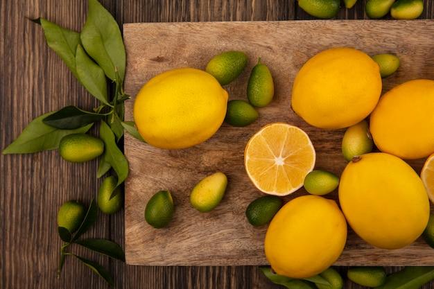 Draufsicht auf reich an vitaminenfrüchten wie kinkans und zitronen lokalisiert auf einem hölzernen küchenbrett auf einer holzwand