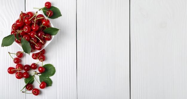 Draufsicht auf reife kirschen und grüne blätter in einer weißen schüssel auf weißem holzhintergrund
