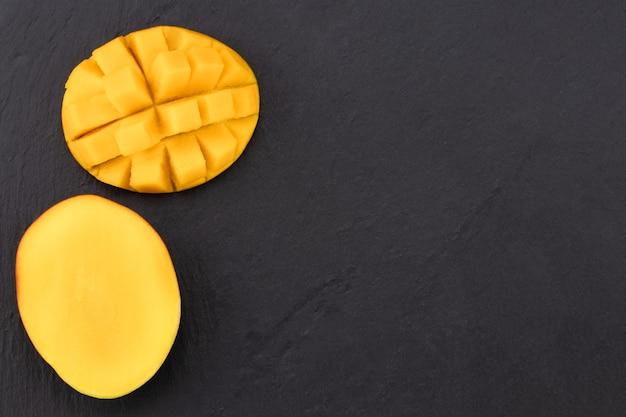 Draufsicht auf reife mango, halbiert und auf dunklem schiefer gewürfelt.