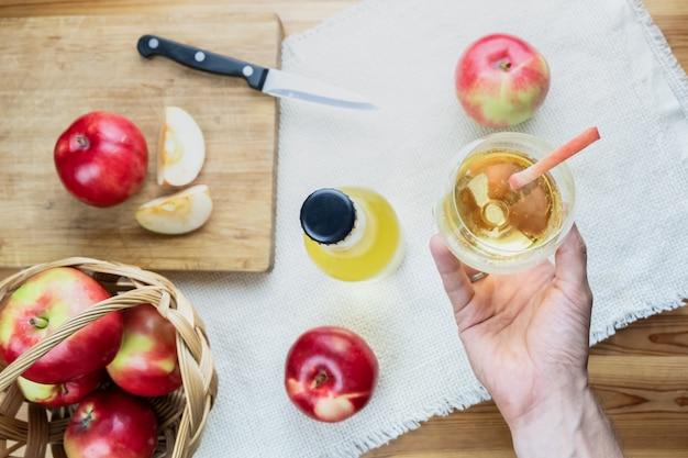 Draufsicht auf reife saftige äpfel und glas cidregetränk auf rustikalem holztisch. sicht der hand, die ein glas hausgemachten cidre und lokal angebaute bio-äpfel hält