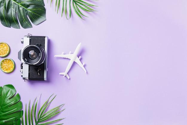 Draufsicht auf retro-kamera, flugzeug, blätter und reiseaccessoires