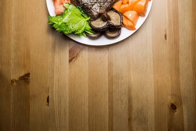 Draufsicht auf rindfleisch mit frischem gemüse