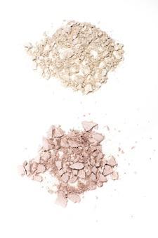 Draufsicht auf rissige rosa und silberne kompakte hervorhebungspulver isoliert auf weißem hintergrund