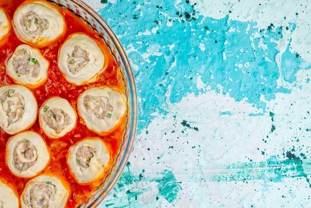 Draufsicht auf rohe fleischige teigteigscheiben mit hackfleisch innen mit tomatensauce in glaspfanne auf blauem schreibtisch