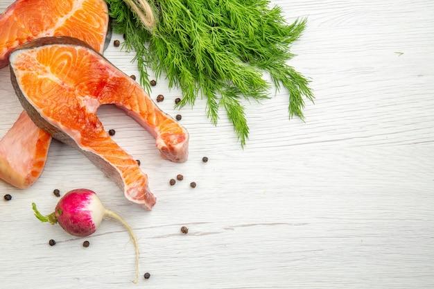 Draufsicht auf rohe fleischscheiben mit grüns und paprika auf weißem hintergrund