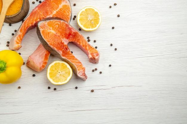 Draufsicht auf rohe fleischscheiben mit zitrone und paprika auf weißem hintergrund