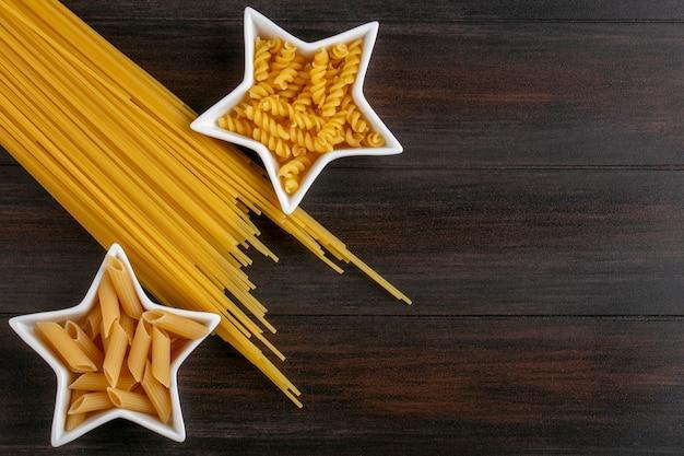 Draufsicht auf rohe nudeln in sternförmigen untertassen mit rohen spaghetti auf einer holzoberfläche