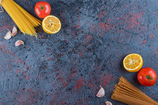 Draufsicht auf rohe nudeln mit frischen roten tomaten und knoblauch auf dunklem hintergrund.