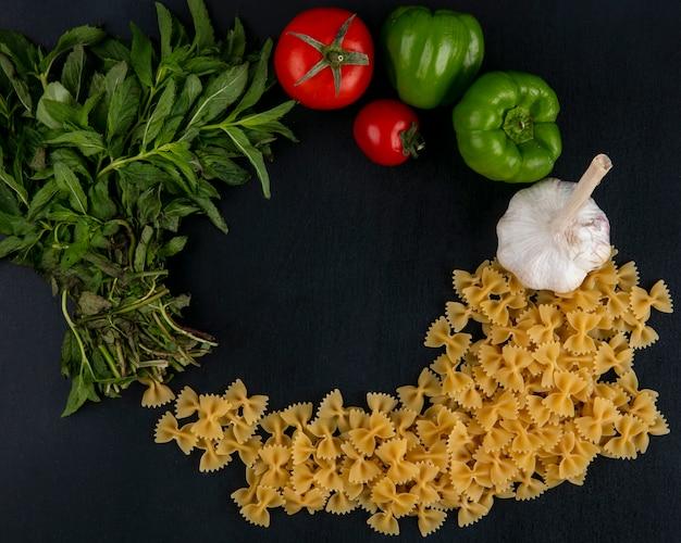 Draufsicht auf rohe nudeln mit tomaten knoblauch und paprika mit minze auf einer schwarzen oberfläche