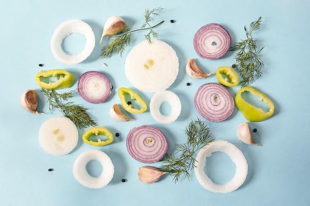 Draufsicht auf rohe zwiebelringe mit gelbem pfeffer, pfefferkörnern, knoblauch und dill auf einer blauen oberfläche