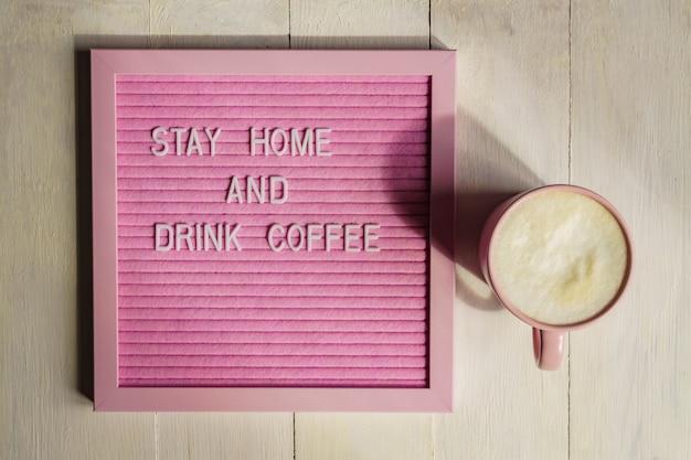 Draufsicht auf rosa tasse mit cappuccino und qoute bleiben sie zu hause und trinken sie kaffee. selbstisolations- und quarantänekampagne zum schutz vor coronavirus-pandämie.