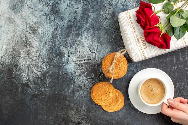 Draufsicht auf rote rose auf geschenkbox und kekse eine tasse kaffee auf der linken seite auf eisigem dunklem hintergrund