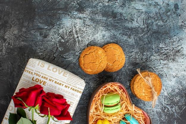 Draufsicht auf rote rose auf schöner geschenkbox mit leckeren macarons und keksen auf eisigem dunklem hintergrund