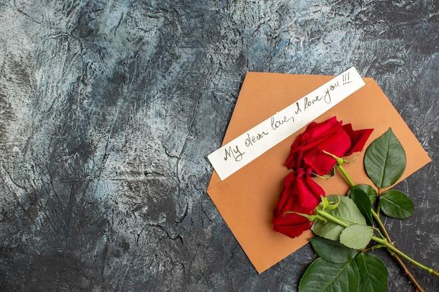 Draufsicht auf rote rosen und umschlag mit liebesbrief auf der linken seite auf eisigem dunklem hintergrund