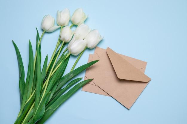 Draufsicht auf rote tulpen und bastelumschlag mit brief, flachgelegt,