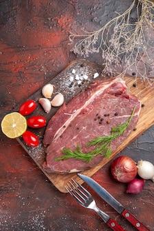 Draufsicht auf rotes fleisch auf holzbrett und knoblauch, grüne zitronenzwiebelgabel und -messer auf dunklem hintergrund