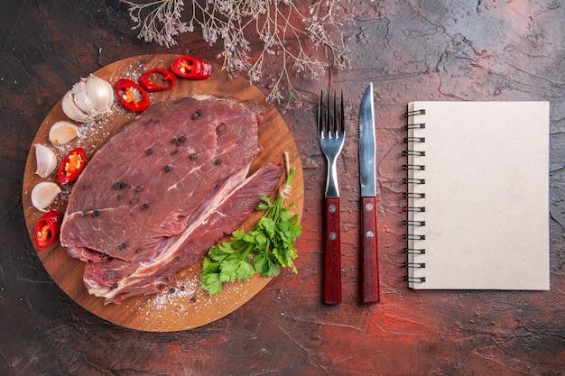 Draufsicht auf rotes fleisch auf holztablett und knoblauch, grüne zitronenpfeffer-zwiebelgabel und -messer und -notizbuch auf dunklem hintergrund