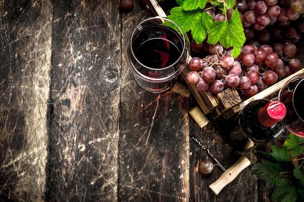 Draufsicht auf rotwein mit einer schachtel trauben