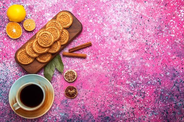 Draufsicht auf runde süße kekse, die mit teezitrone und zimt auf der rosa oberfläche ausgekleidet sind
