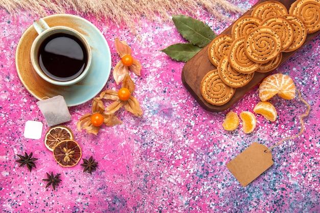 Draufsicht auf runde süße kekse mit tasse tee und mandarinen auf der rosa oberfläche