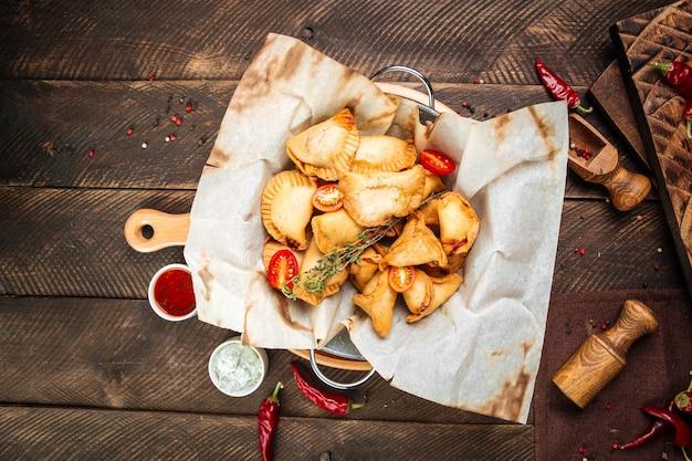 Draufsicht auf russische snacks mini gebratene kuchen chebureki mit sauce auf dem holztisch