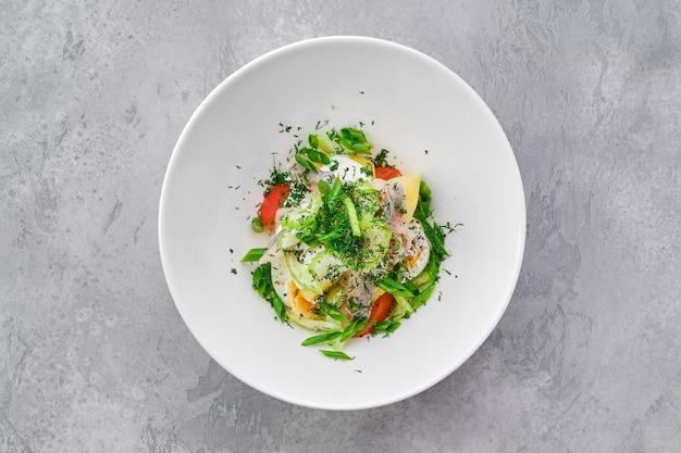 Draufsicht auf salat mit hering, salzkartoffel, zwiebel, sellerie und ei
