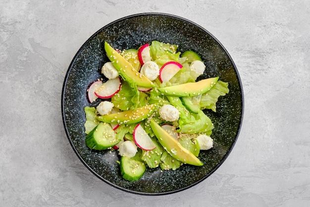 Draufsicht auf salat mit salat, avocado, rettich und mozzarella angemacht mit sesam