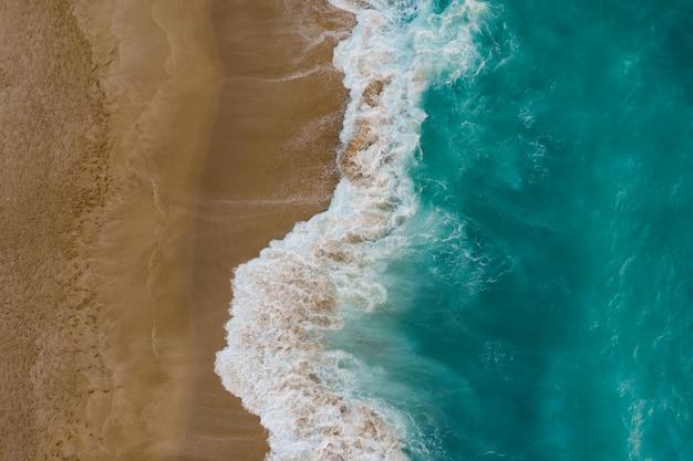 Draufsicht auf sand, der meerwasser trifft