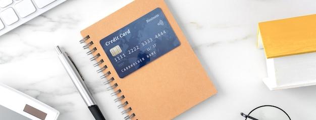 Draufsicht auf schätzung und zahlung der haussteuer mit taschenrechner und kreditkarte aus dem internet.