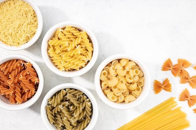 Draufsicht auf schalen mit verschiedenen ungekochten nudeln. mediterranes essen