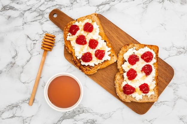 Draufsicht auf schneidebrett mit toast und himbeeren