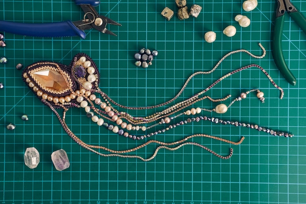 Draufsicht auf schöne brosche mit perlen auf dem grünen tisch