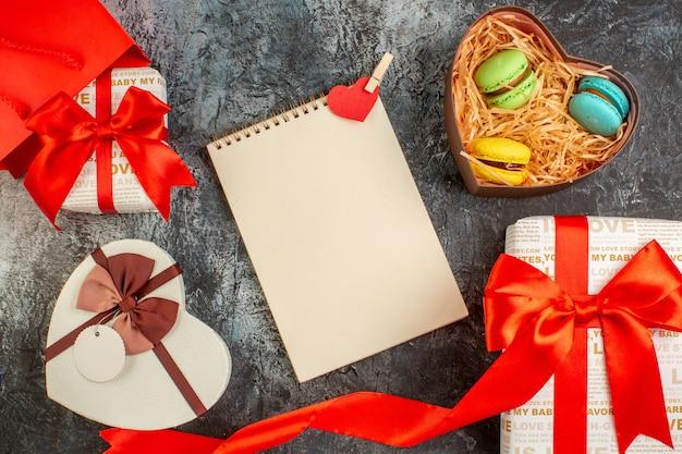 Draufsicht auf schöne geschenkboxen, die mit rotem band und köstlichen makronen in herzförmigem spiralnotizbuch auf eisigem dunklem hintergrund gebunden sind