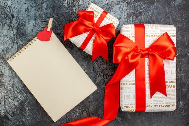 Draufsicht auf schöne geschenkboxen mit rotem band in verschiedenen größen notizbuch auf eisigem dunklem hintergrund