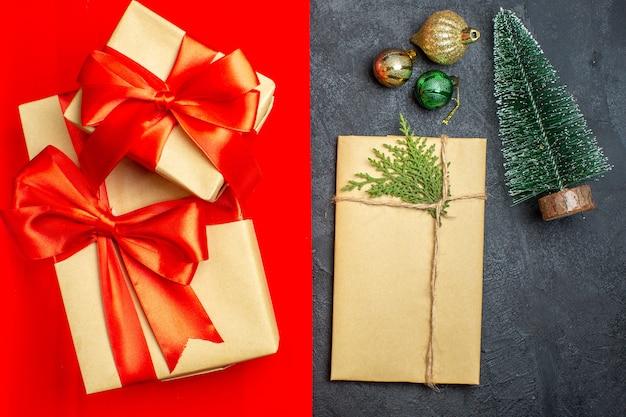 Draufsicht auf schöne geschenke mit bogenförmigem band neben tannenzweigdekorationszubehör auf einem roten hintergrund