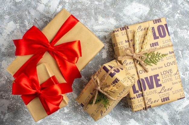 Draufsicht auf schöne weihnachtsgeschenke mit großen und kleinen verpackten geschenken mit liebesaufschrift und rotem band auf der eisoberfläche