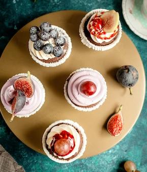 Draufsicht auf schokoladencupcakes, verziert mit vanillecremefeigentrauben und blaubeeren