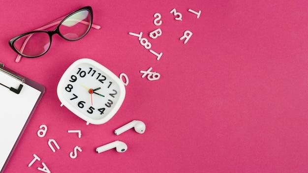 Draufsicht auf schreibtisch mit uhr und brille