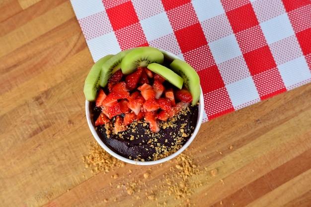 Draufsicht auf schüssel mit erdnüssen, kiwi, erdbeere und açai cremig auf einer serviette mit karodruck