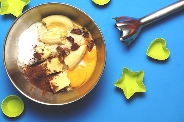 Draufsicht auf schüssel mit vorbereitung für bio-bananenkuchen neben gebäckformen und geformtem mixer Premium Fotos