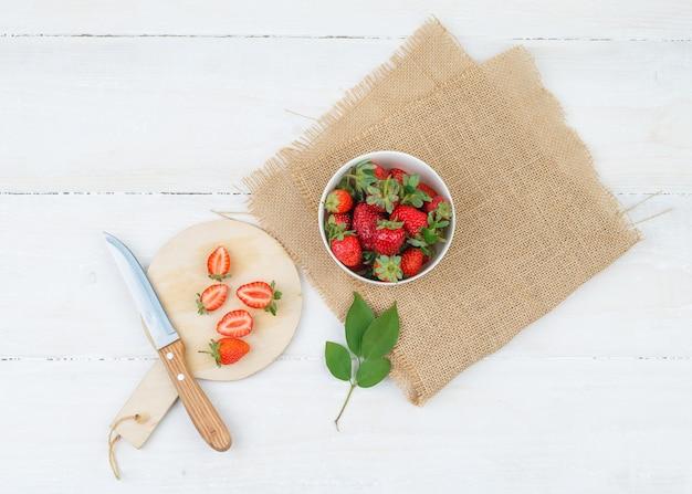 Draufsicht auf schüssel und teller mit erdbeeren